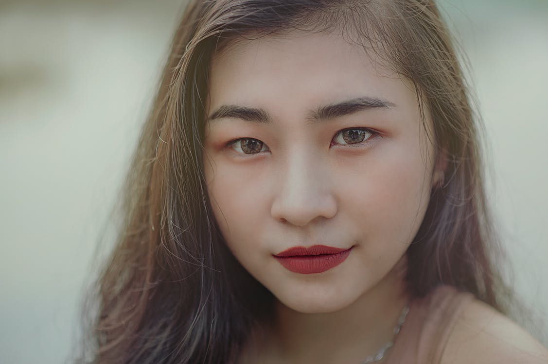 Close-Up Photography of Woman Wearing Red Lipsticks