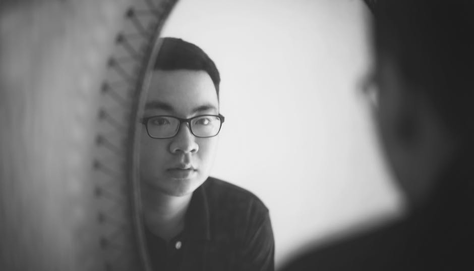 Monochrome Photography of a Man Looking In front of Mirror
