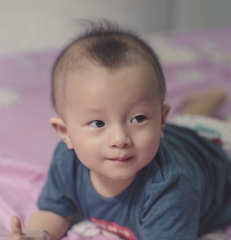 Photography of Cute Baby Laying on the Bed