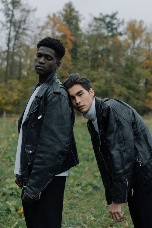 Man in Leather Jacket Leaning on Man's Back