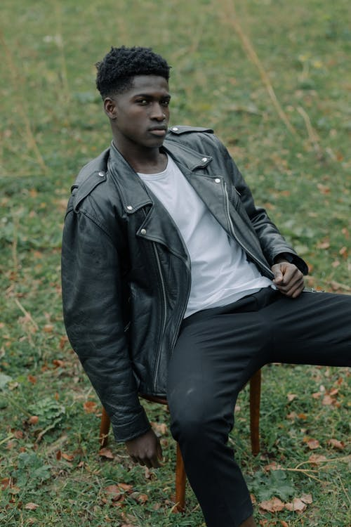 Man in Black Leather Jacket Sitting on a Stool