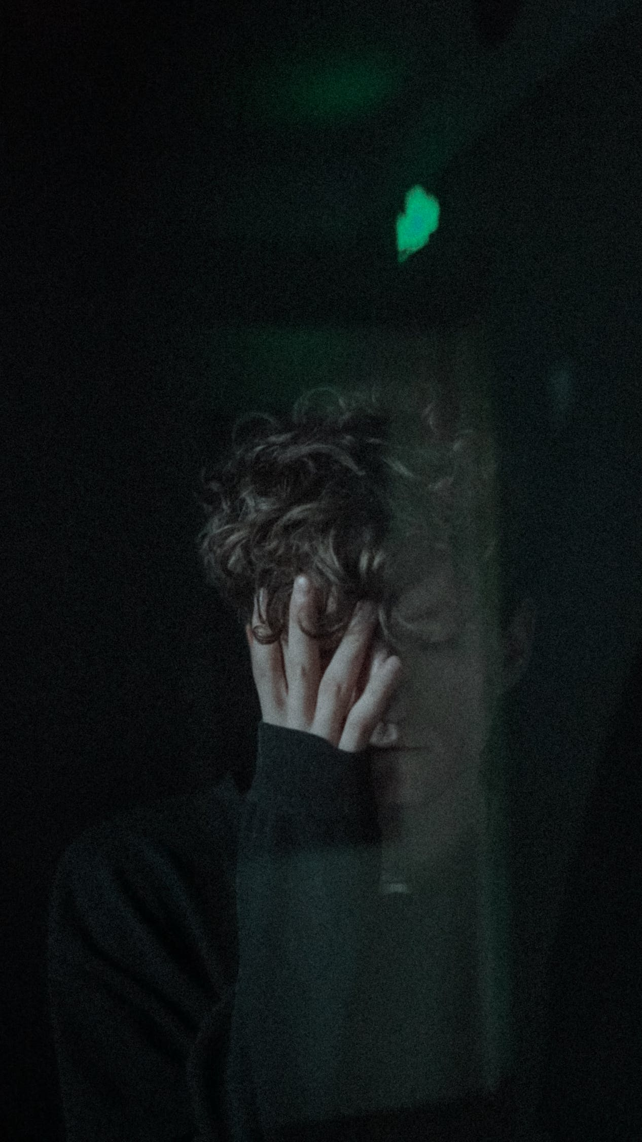 Through window of depressed unhappy male with closed eyes covering face with hand while standing in dark room near glass