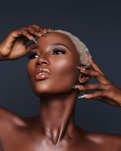 Confident African American female with short hair and makeup with long lashes touching face with manicured nails and looking away against black background