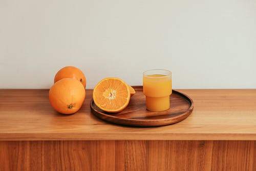 A Fresh Orange Juice on a Brown Wooden Table