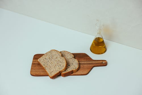 Two Slices of Wheat Bread on a Wooden Serving Board