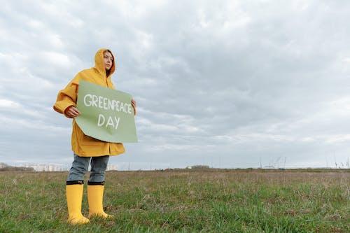 Woman Holding a Green Slogan