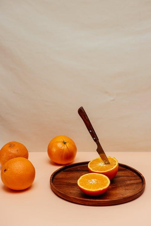茶色の木製丸皿にオレンジ色の果実