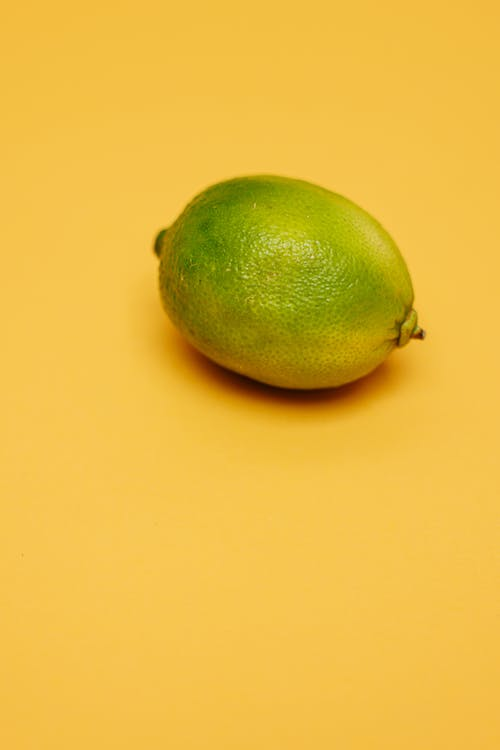 Green Lime on Yellow Surface