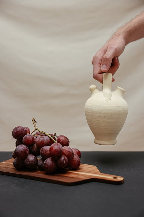 Person Holding White Ceramic Vase with Grapes on Brown Wooden Chopping Board