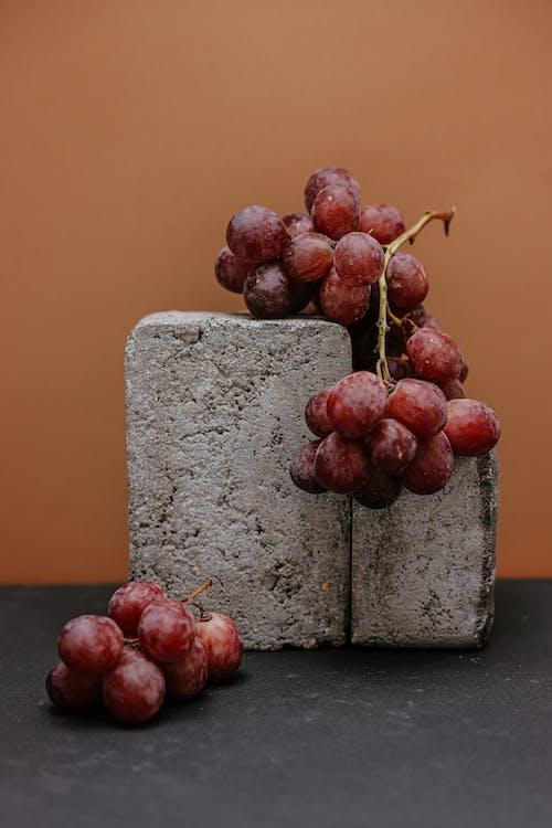 A Close-Up Shot of Grapes and Concrete Blocks