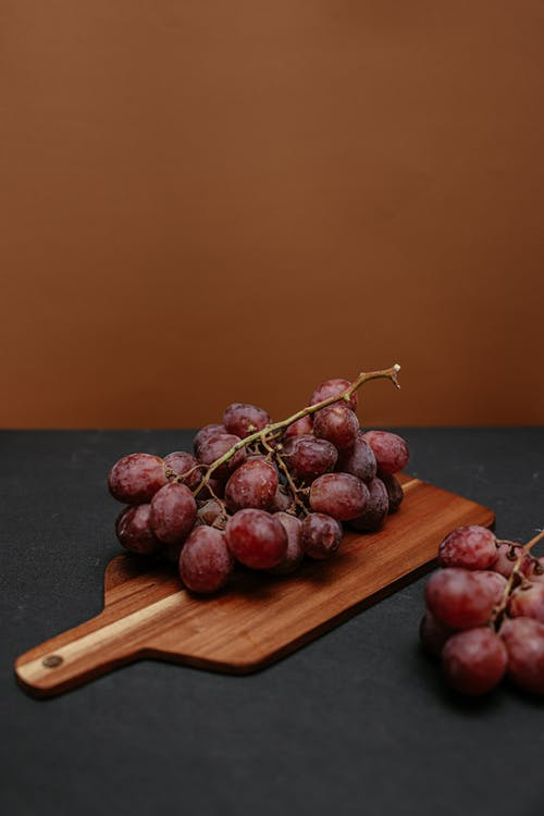 Red Round Grapes on Brown Wooden Chopping Board