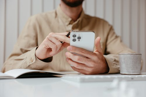 Een Man In Bruine Lange Mouwen Die Zijn Mobiele Telefoon Gebruikt
