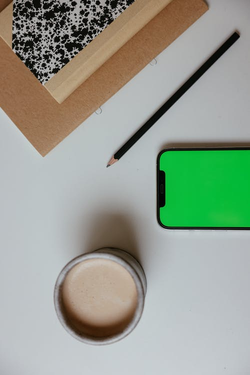A Pencil In Between of Smartphone And Notebooks