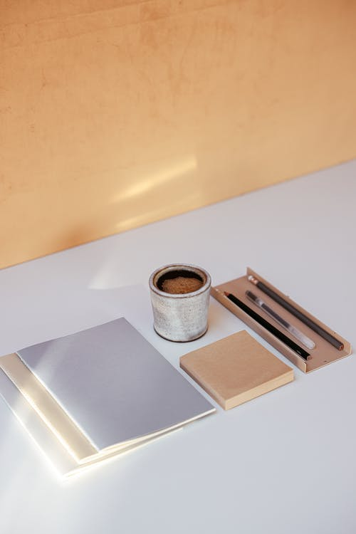A Cup of Coffee and Writing Materials on a Table
