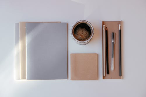 A Flatlay of a Cup of Coffee and Writing Materials