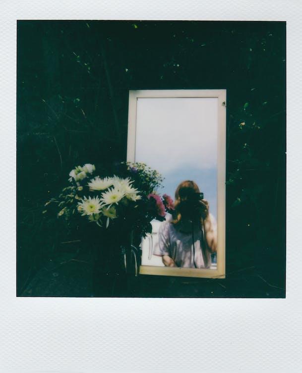 Woman in White Long Sleeve Shirt Standing Beside White Wooden Framed Glass Window