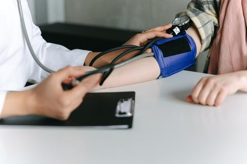 A Healthcare Worker Measuring a Patient's Blood Pressure Using a Sphygmomanometer