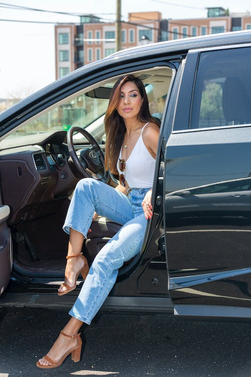 Woman in White Tank Top and Blue Denim Jeans Sitting on Black Car Seat