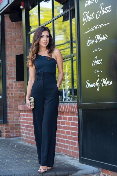Woman in Black Sleeveless Dress Standing Beside Black Wooden Door