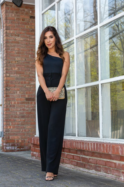 Woman in Black Sleeveless Dress Standing Beside Brown Brick Wall