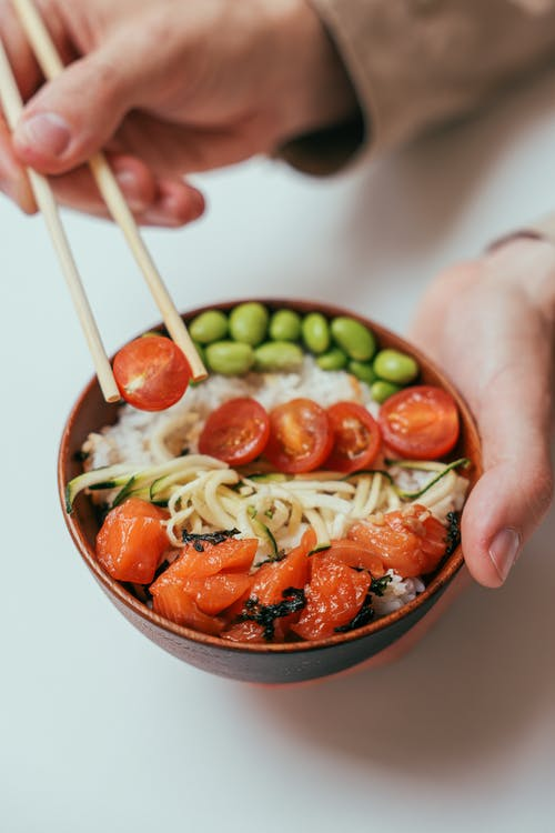 Person Holding a Chopstick and Rice Bowl