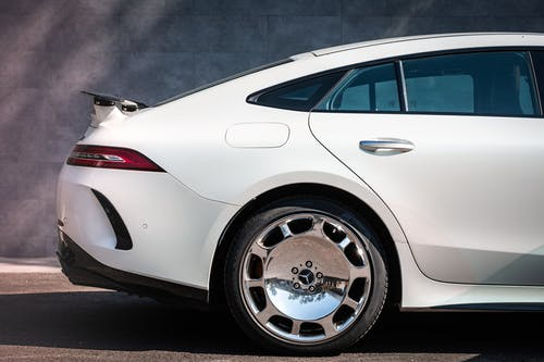 White Car with Chrome Wheels Parked on the Road