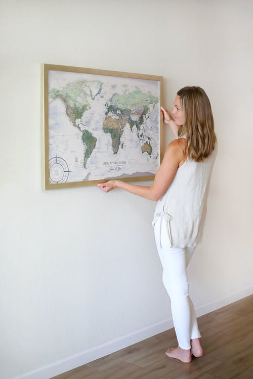 Woman in White Sleeveless Top and White Leggings Holding Frame Hanging on Wall