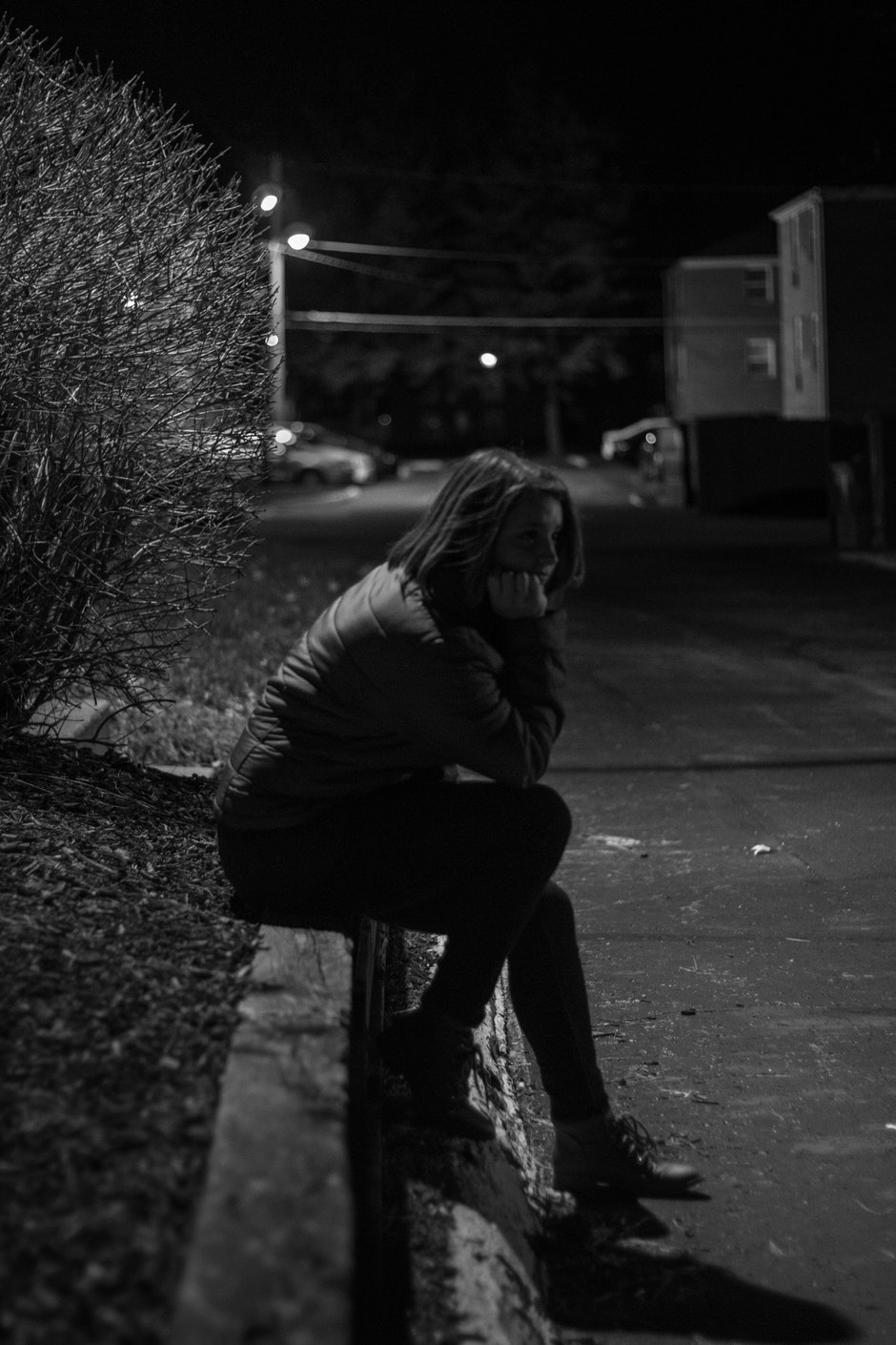 Woman Wearing Jacket Sitting on Concrete during Night Time