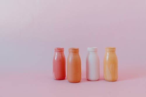 2 Orange Bottles on White Surface