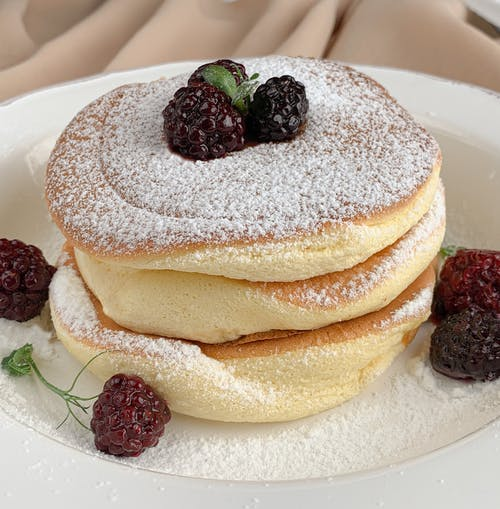 Close-Up Photo of Pancakes with Raspberries and Powdered Sugar
