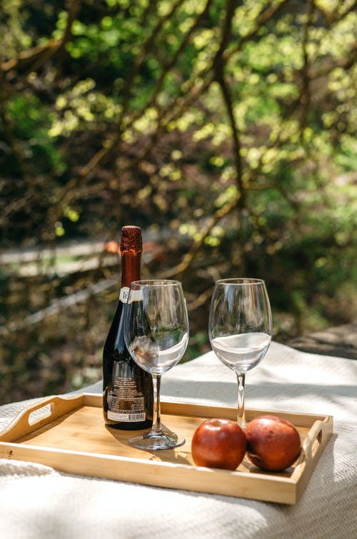Elegant crystal glasses with bottle of wine and apples served on wooden tray on table in green garden on sunny day