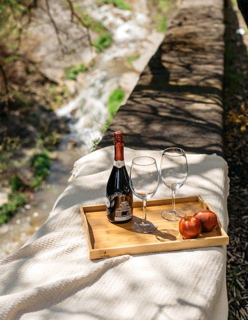 Wine Bottle Beside Wine Glass on Brown Wooden Chopping Board