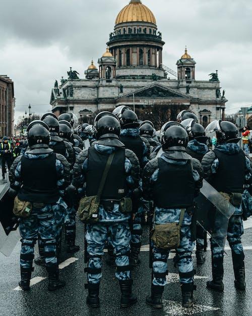 Group of Men in Black Helmet Standing on Gray Concrete Floor