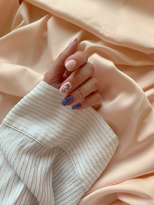A Hand With Manicured Nails on White Textile