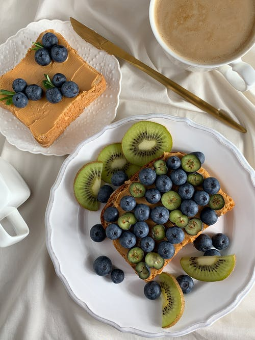 Sliced of Cake With Blue Berries on White Ceramic Plate