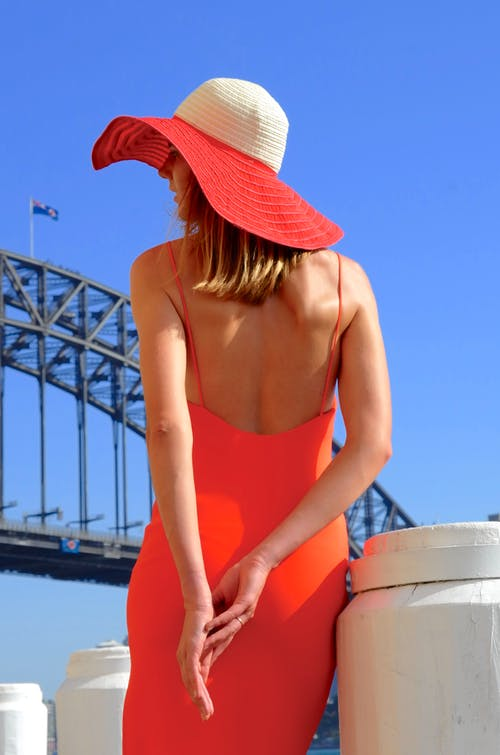 Woman in Red Spaghetti Strap Top Wearing White Fedora Hat