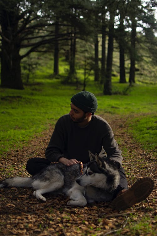 Man in Brown Hoodie and Black and White Siberian Husky