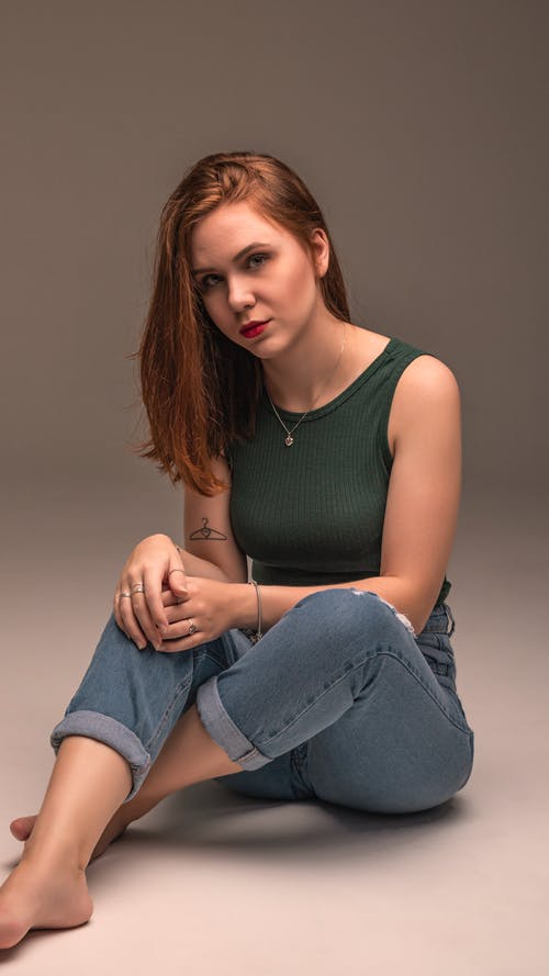 Woman in Green Tank Top and Blue Denim Jeans