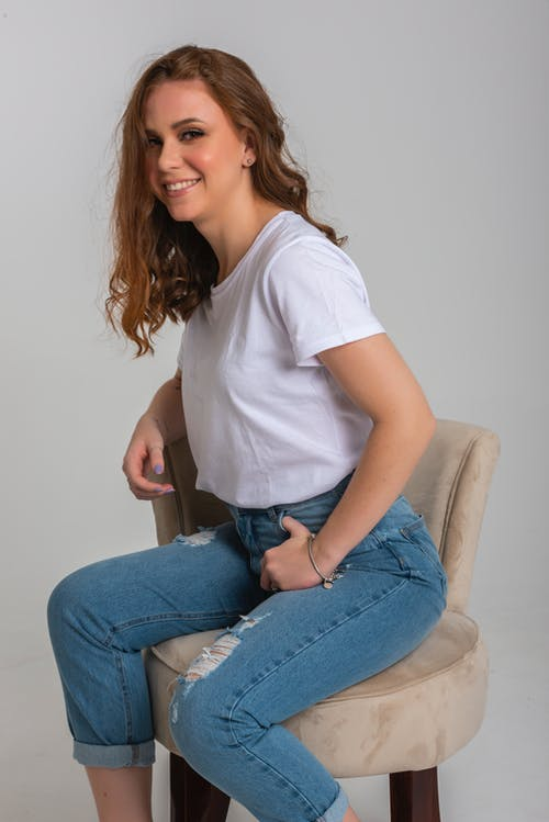 Woman in White Crew Neck T-shirt and Blue Denim Jeans Sitting on White Chair