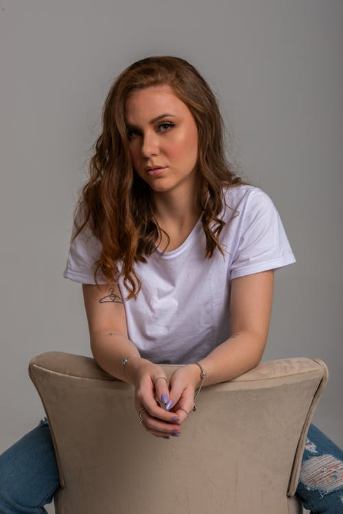 Woman in White Crew Neck T-shirt Sitting on Chair