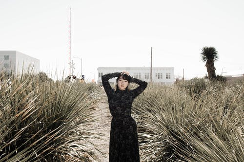 Woman in Black Long Sleeve Dress Standing on Green Grass Field