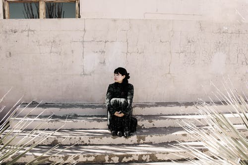 Woman in Black Jacket Sitting on Snow Covered Ground