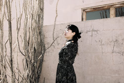 Woman in Black and Gray Floral Dress Standing Beside White Wall