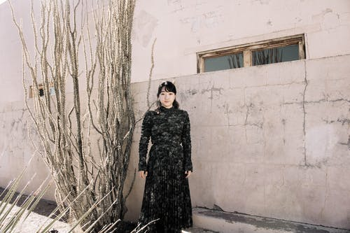 Woman in Black Dress Standing Beside White Wall