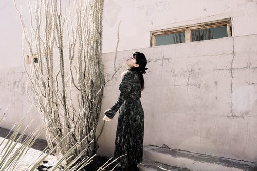 Woman in Black Long Sleeve Dress Standing Beside White Wall