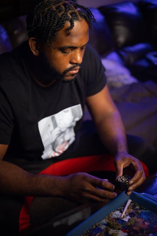 Man in Black Crew Neck T-shirt Holding White Textile