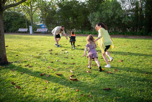 A Family Playing on the Green Grass Field