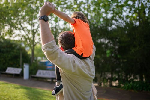 A Man Carrying a Child on His Shoulders
