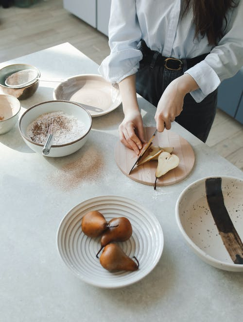 Person in White Dress Shirt Slicing Brown Bread on White Ceramic Plate