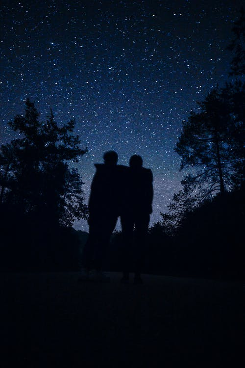 Silhouette of Man and Woman Standing on Road during Night Time